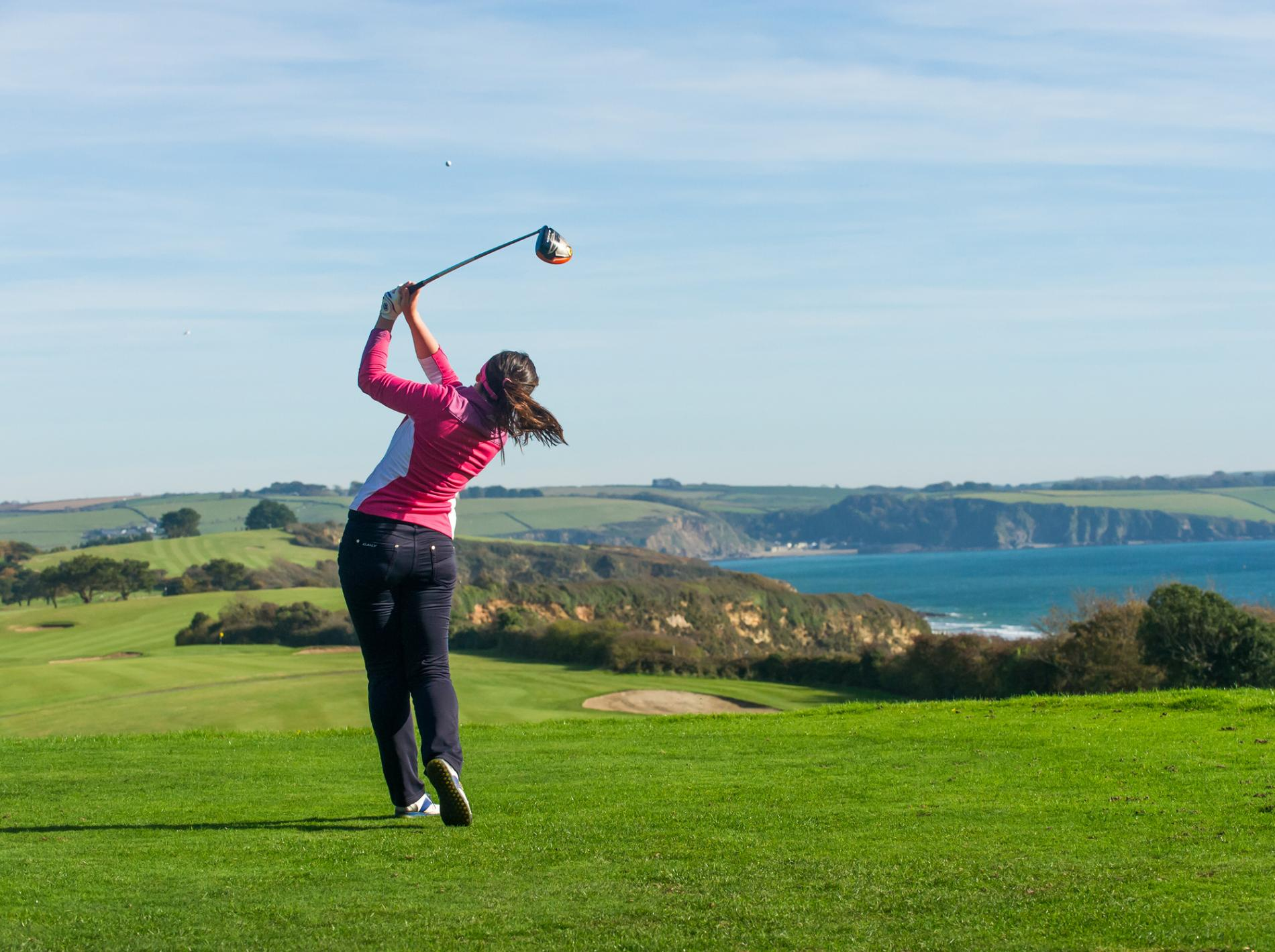 lady golfer taking shot on 1st tee carlyon bay